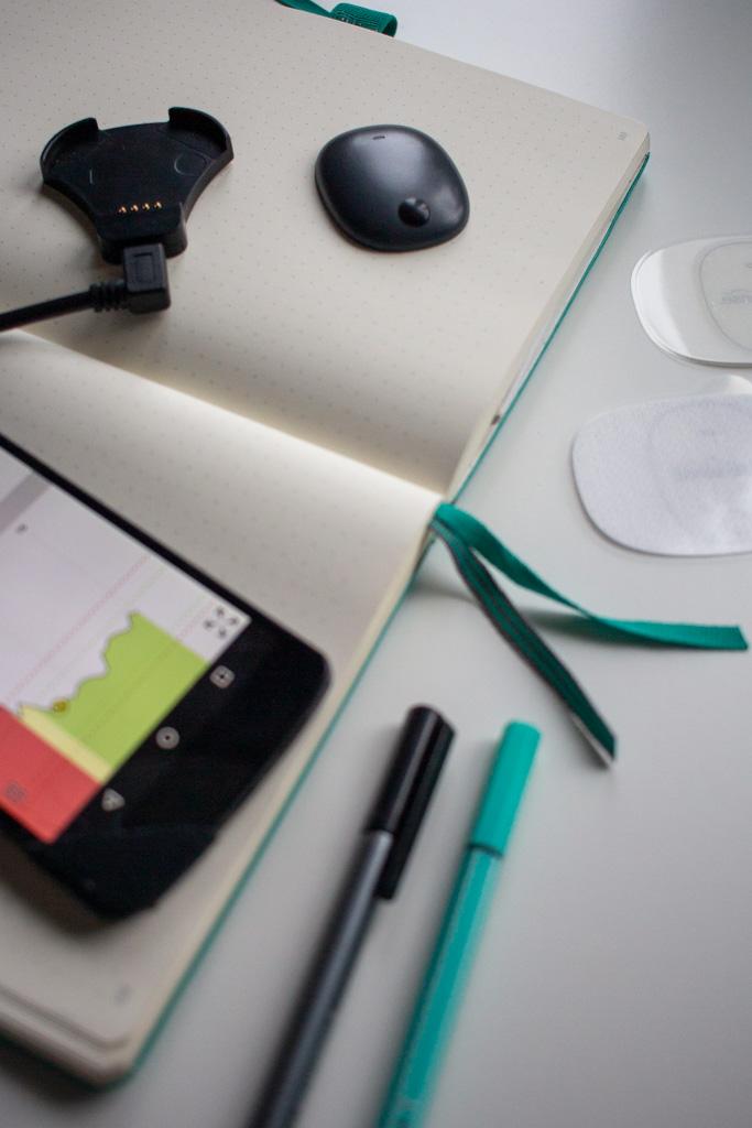 Auf einem aufgeschlagenem Notizbuch liegt im oberen Teil des Bildes der Transmitter und links daneben die zugehörige Ladeschale. Im unterem Bereich des Bildes ist links ein Teil eines Smartphones zu sehen und mittig zwei Stifte.