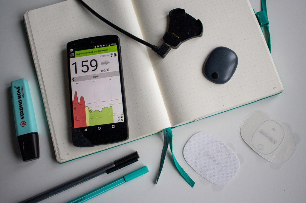 Auf einem aufgeschlagenem Notizbuch liegt der Tranmitter und das Ladegrät des Eversense XL, sowie ein Smartphone, auf dem man Glucosewerte sehen kann.